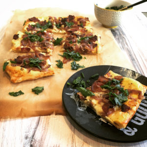 Bacon and Red Onion Tart on a black plate and wood cutting board