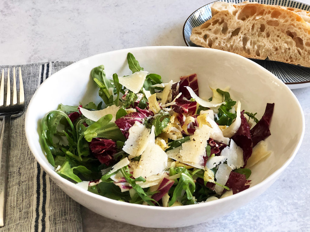 Italian Tricolore Salad in a white bowl with italian bread on the side