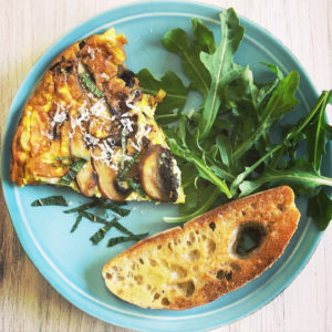 Mushroom Frittata with Gruyere Cheese on late with toasted bread and arugula salad