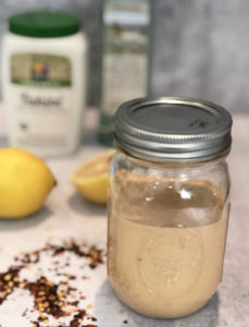 Lemon Tahini Dressing with ingredients in background