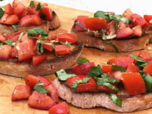 Summer appetizer: Bruschetta with Tomato and Basil served on wooden platter