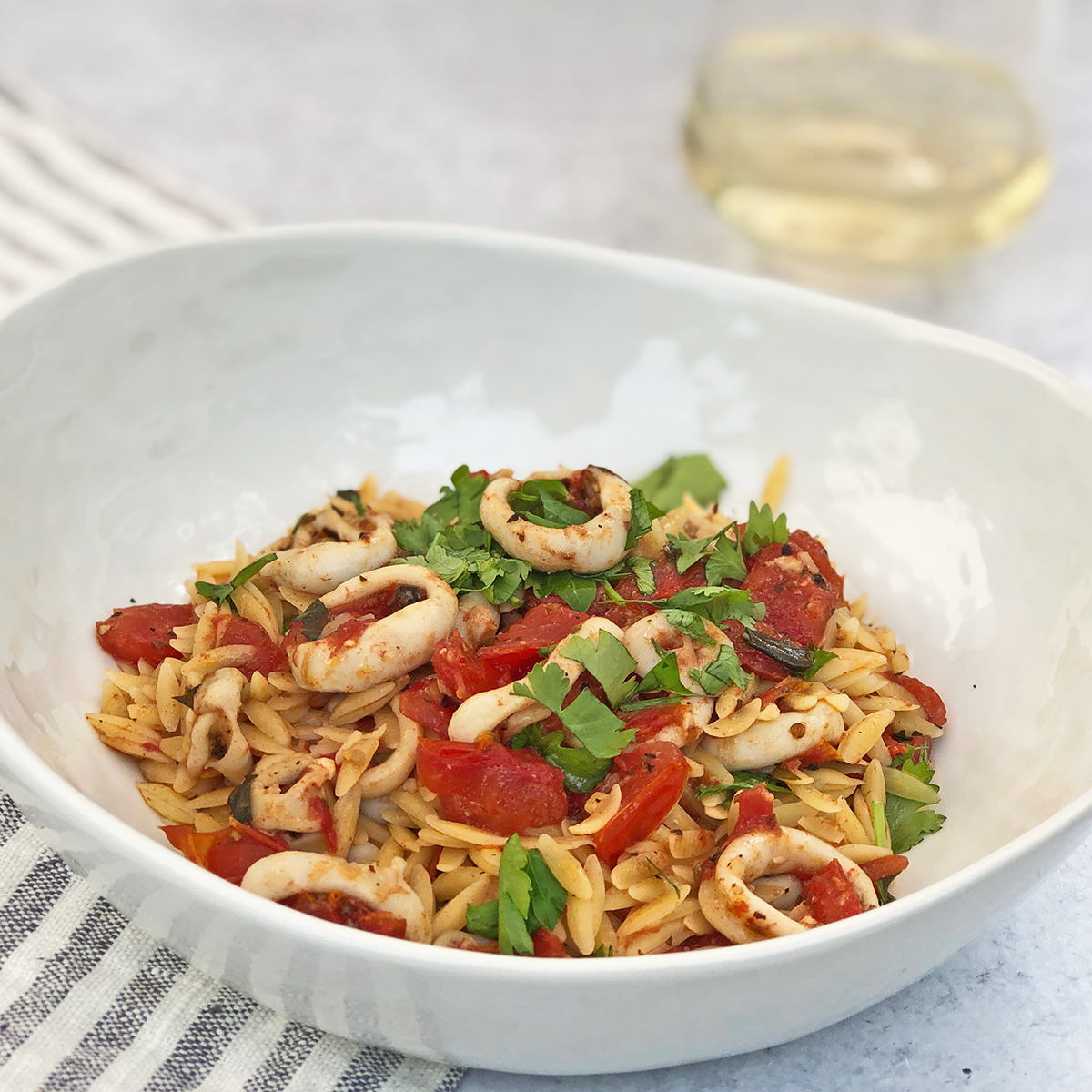 Orzo Pasta with Calamari and Tomato on a table with a glass of Sauvignon Blanc