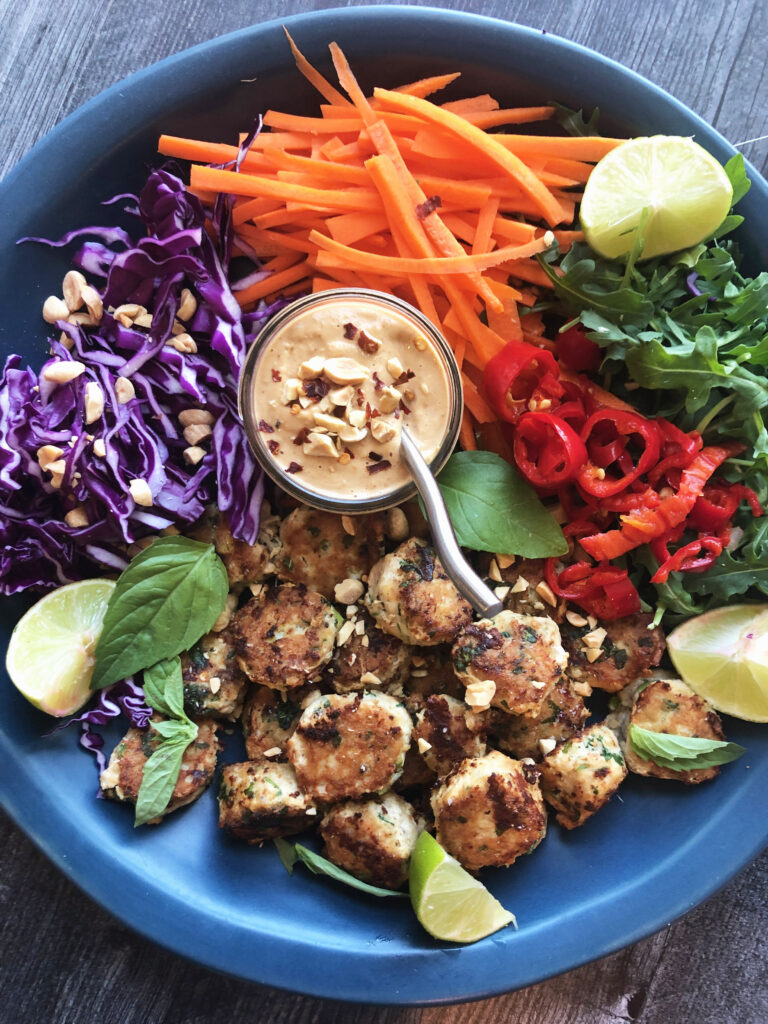 Chicken Meatballs with Peanut Sauce served on a platter with thinly sliced carrots, purple cabbage and arugula